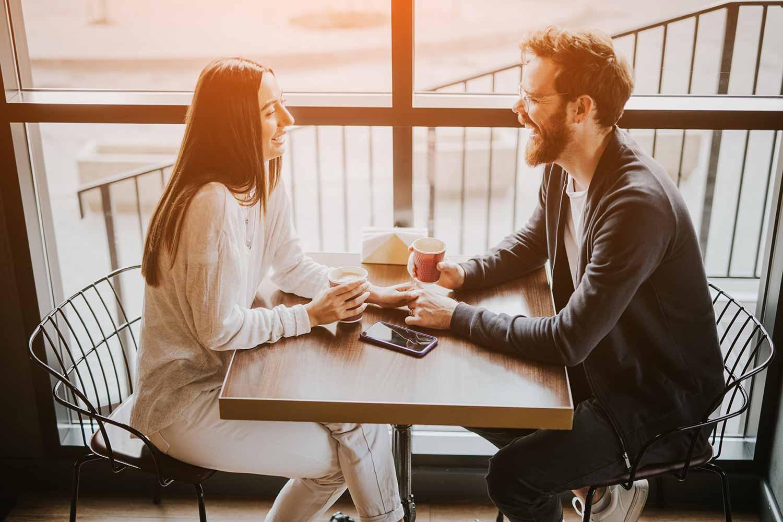 Fröhliches junges Paar mit Kaffee beim ersten Date