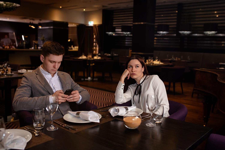 Junger Mann und junge Frau gelangweilt am Restauranttisch